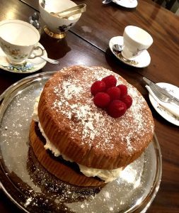 Gluten Free Victoria sponge cake filled with cream and jam, topped with raspberries and dusted with icing sugar