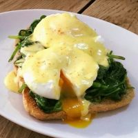 Eggs Benedict - poached eggs on a bed of spinach served with toast and hollandaise sauce